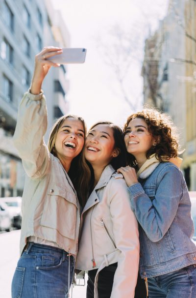 Cheerful young diverse women in casual clothes taking selfie on smartphone while standing on city street in sunny spring day,Nutricentials